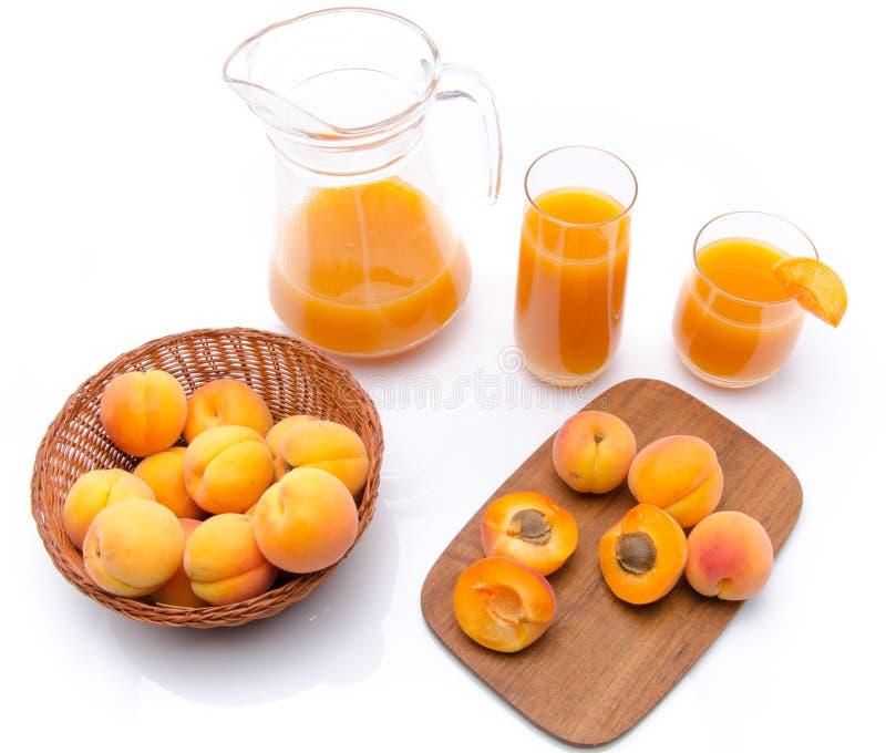 Кувшин и стекла сока абрикоса с всем и отрезанным зрелым apri стоковые изображения rf