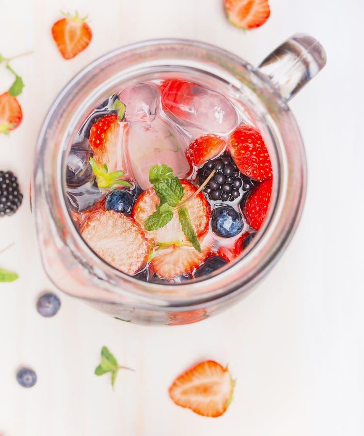 Кувшин с ягодами мочит и кубами льда на белой деревянной предпосылке, взгляд сверху, конце вверх стоковая фотография rf