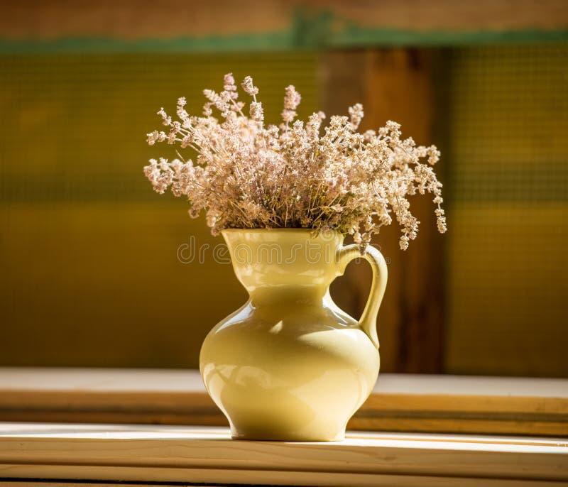 Кувшин с wildflowers стоит на деревянном столе в ro стоковая фотография