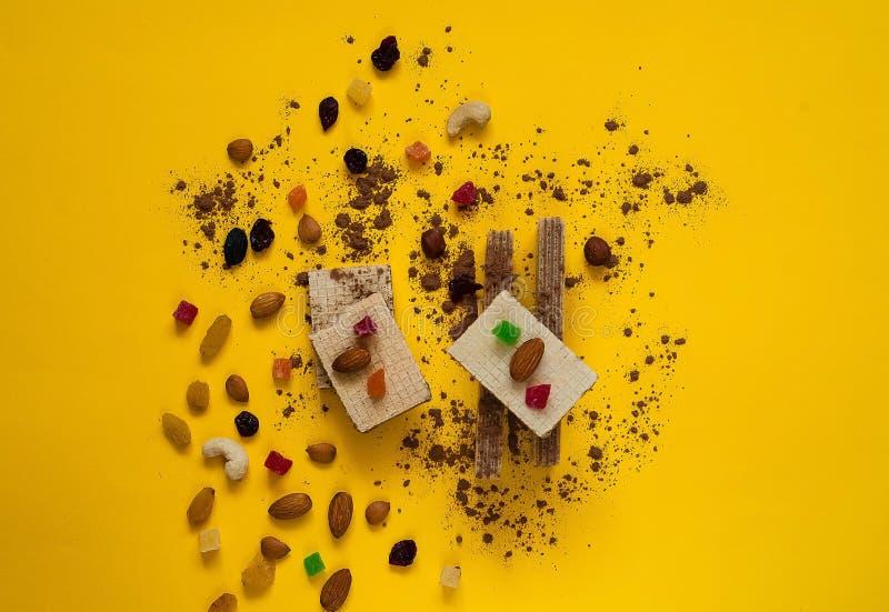 Кудрявые вафли с шоколадом, гайки на яркой желтой предпосылке Помадки концепция, космос экземпляра стоковая фотография