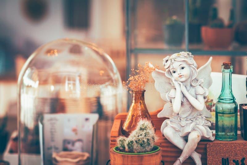 Кукла купидона штукатурки римская сидя на меньшей деревянной коробке около кактуса в кофейне стоковое изображение rf
