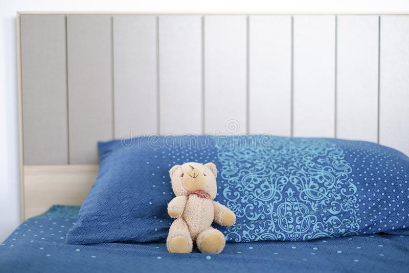 Кукла медведя спать сиротливый на кровати стоковые изображения rf