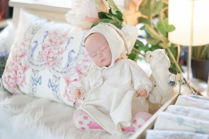 Куколка Мягкий фокус и мечтательное влияние милой куколки спать рядом со статуей кролика стоковые фото