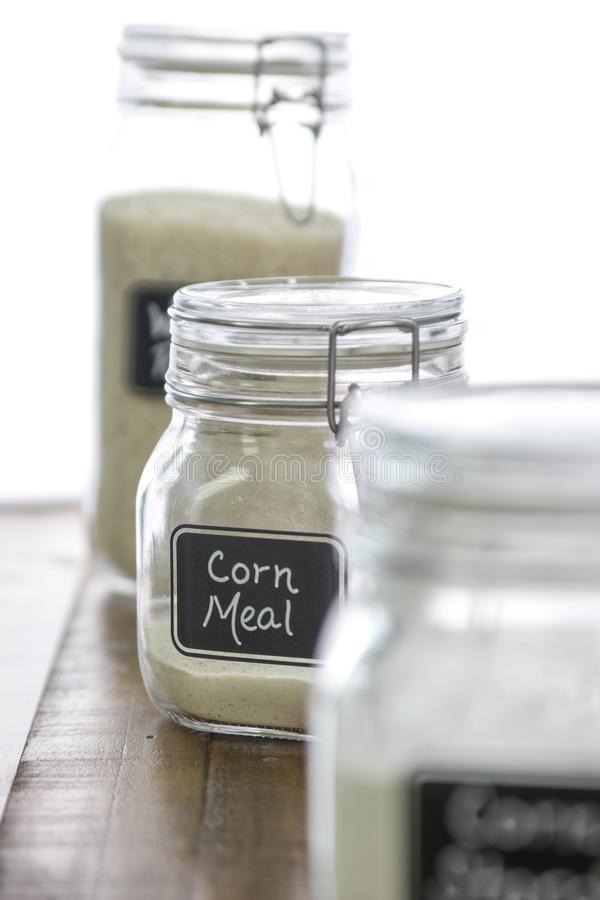 Кукурузная мука в опарнике с другими печь ингредиентами дальше из предпосылки фокуса стоковые фотографии rf