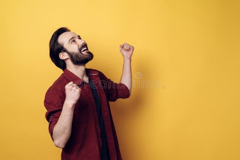 Кулаки счастливого привлекательного бородатого человека обхватывая стоковое фото rf