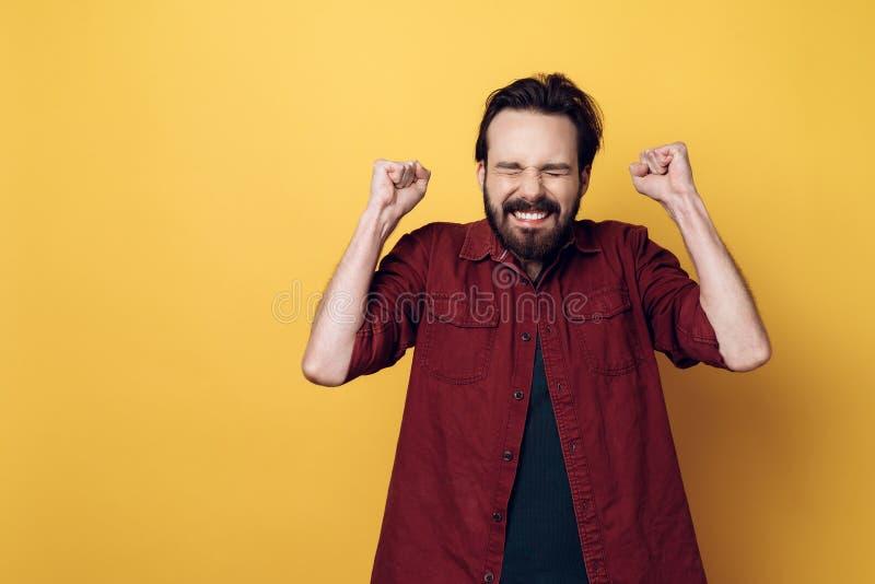 Кулаки счастливого привлекательного молодого бородатого человека обхватывая стоковая фотография
