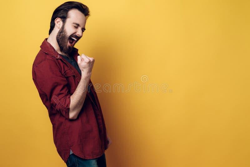 Кулаки счастливого привлекательного молодого бородатого человека обхватывая стоковое изображение rf