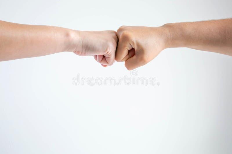 Кулаки bumping совместно на белой предпосылке стоковое изображение