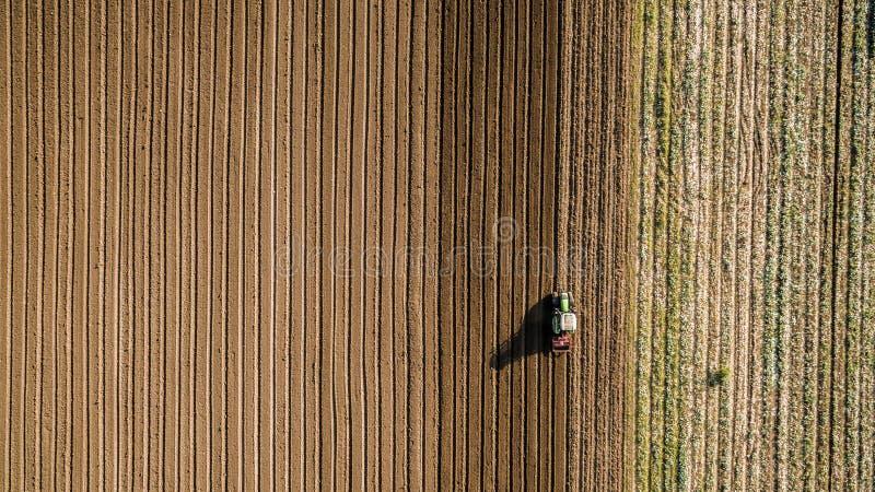 Культивировать трактора и мучительное поле на весеннем сезоне стоковая фотография