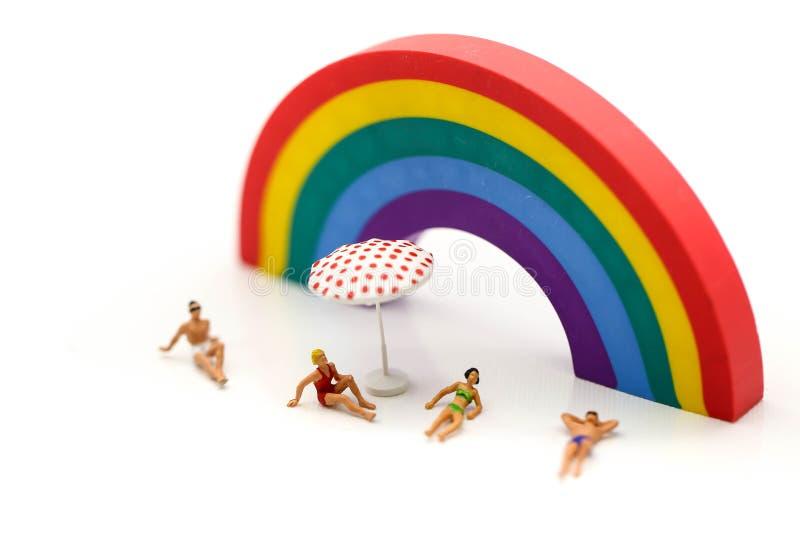 Купальник миниатюрных людей нося ослабляя с backgrou радуги стоковые фото