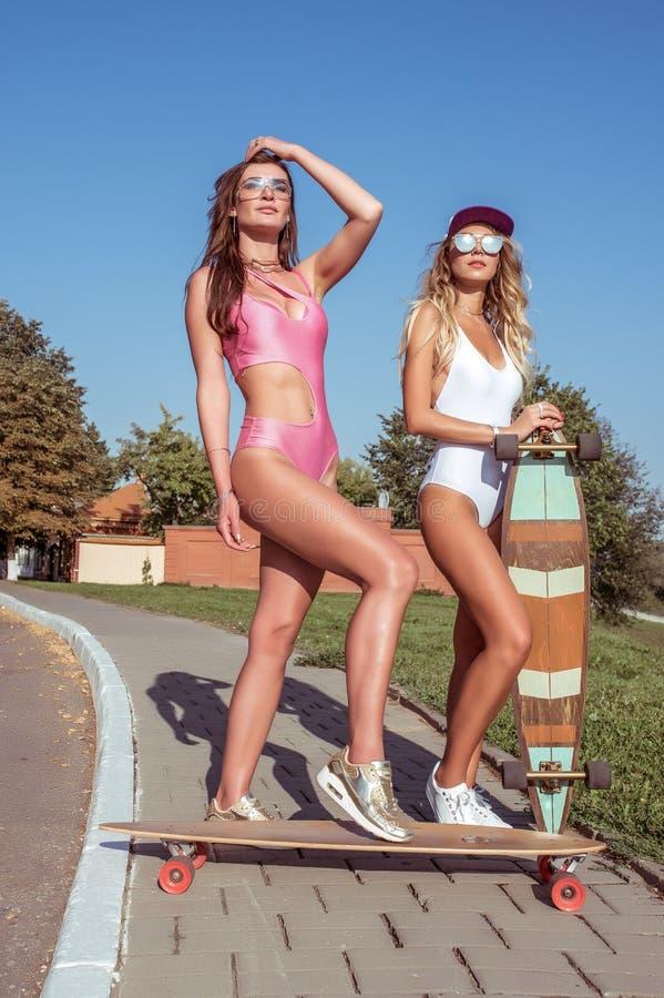 2 купального костюма тела девушек девушек, загорают город лета Дорога стойки В скейтбордах рук, longboards Город остатков стоковые изображения rf