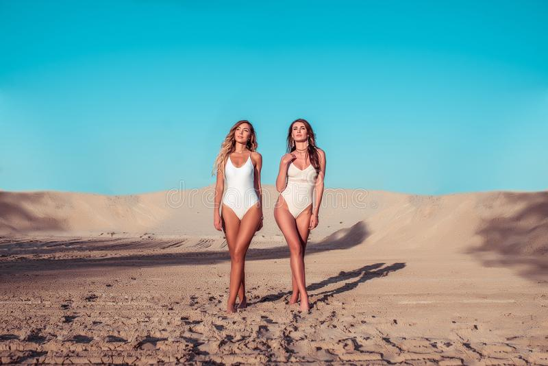 2 купального костюма тела девушек девушек, загорают город лета Идущ вдоль пляжа, туристское море остатков, стиль и стоковое изображение