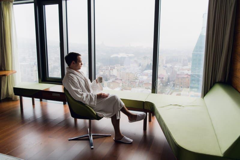 Купальный халат молодого красивого беспечального человека нося около современного полнометражного окна наслаждаясь чашкой кофе по стоковые изображения