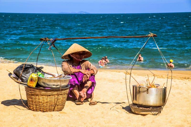 Купцы продают местную еду к туристам на пляже стоковая фотография
