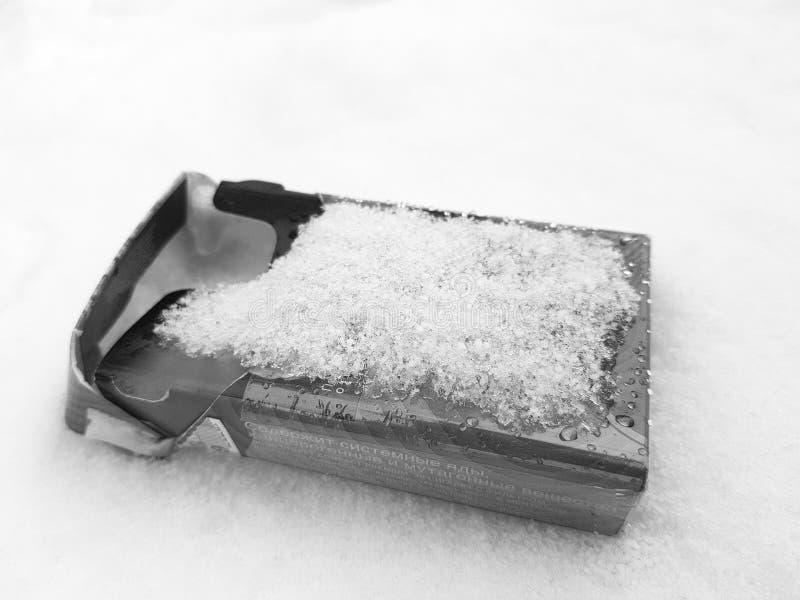 Курение - пакет сигареты в снеге в зиме стоковые фото