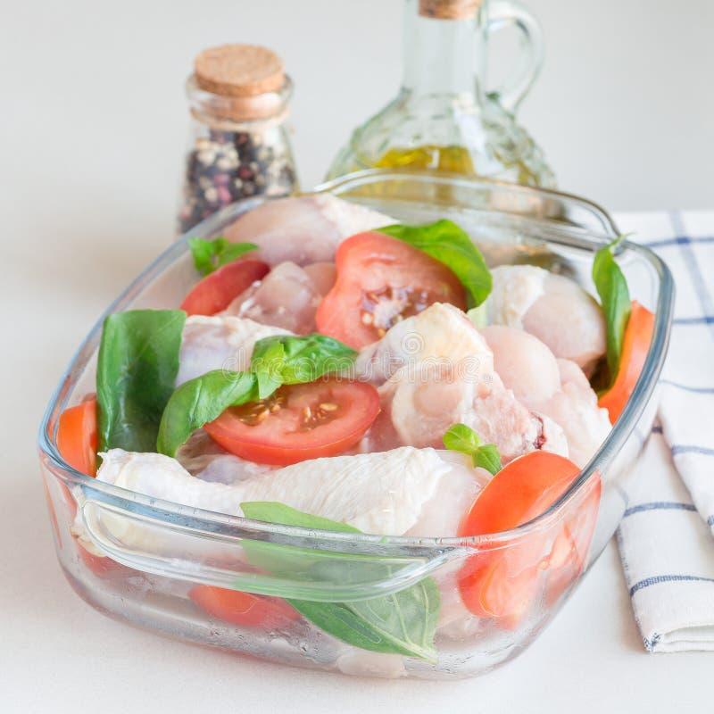 Куриные ножки ARaw сырые, drumsticks с томатами и базилик в стеклянном подпирая блюде, квадрате стоковое фото