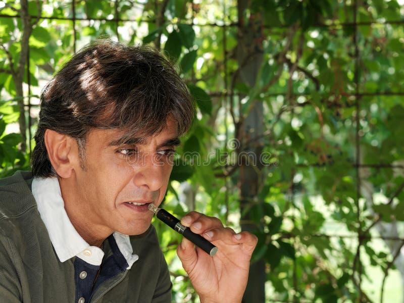 Курильщик электронной сигареты в тусклом свете стоковое фото rf