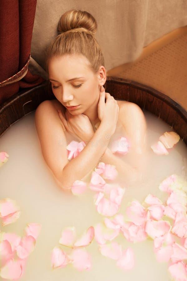 Курорт Девушка принимает ванну с солью и лепестками розы моря стоковое изображение rf