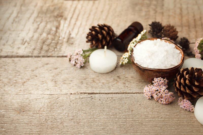 Курорт и установка здоровья с солью моря, сутью масла, конусами и свечой на деревянной предпосылке Концепция здоровья осени паден стоковые изображения