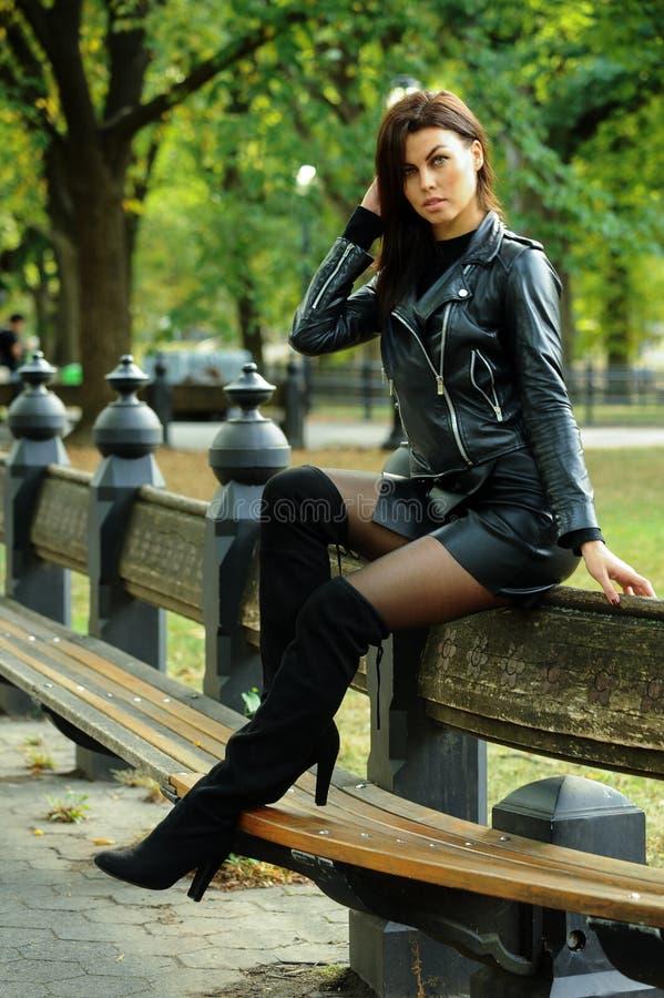 Куртка молодой женщины нося кожаная, мини юбка и ботинки сверх-колена представляя на осени паркуют стоковая фотография rf