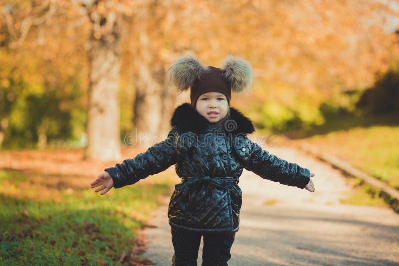 Куртка пальто моды toothsome маленькой девочки штыря-вверх тележки нося стильная черная и внушительная шляпа одевают представлять стоковые фото