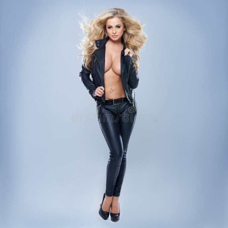 Куртка сексуальной белокурой женщины нося стоковое изображение