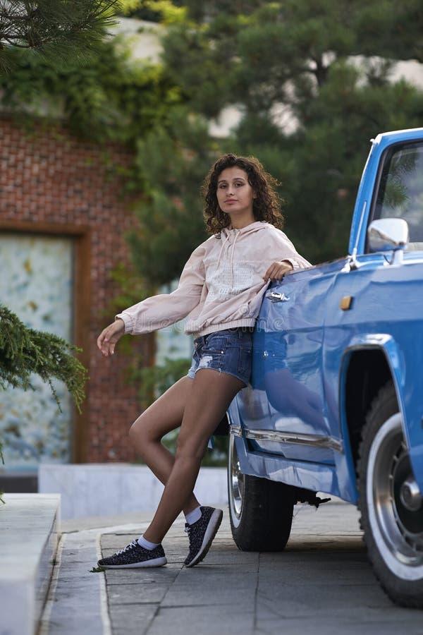 Курчавая девушка и голубой cabriolet стоковое изображение rf