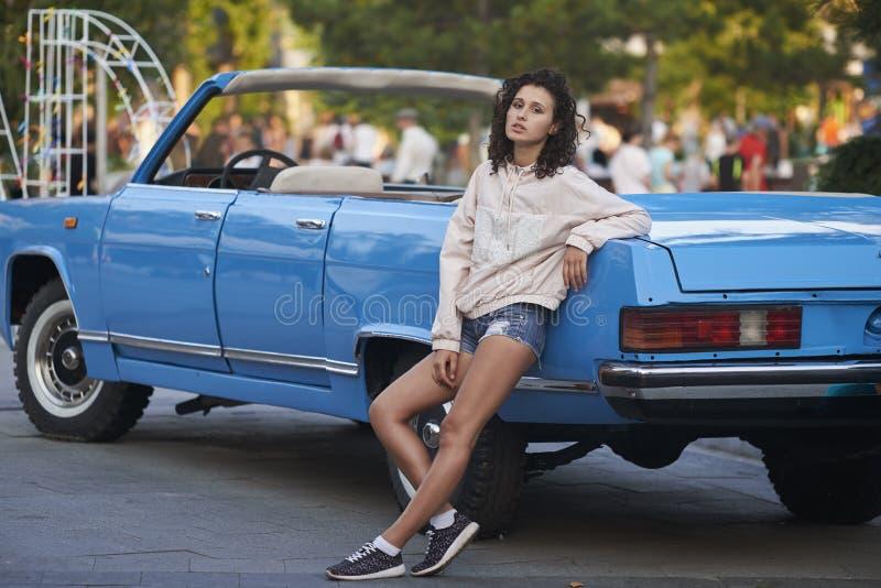 Курчавая девушка и голубой cabriolet стоковые изображения rf