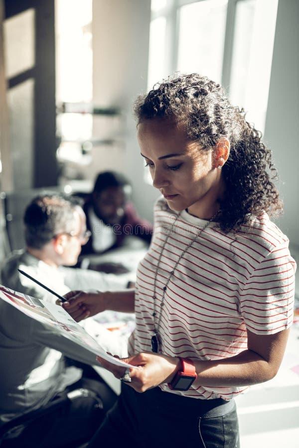 Курчавая секретарша читая документы стоя около ее босса стоковые фото
