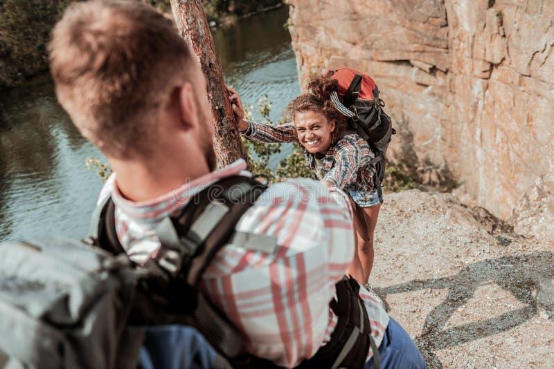 Курчавая темн-с волосами женщина при рюкзак чувствуя благодарный для ее человека помогая ей стоковые фото