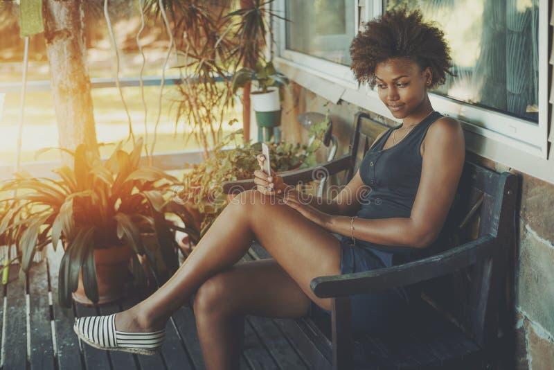 Курчавая черная девушка с телефоном на стенде стоковое фото rf