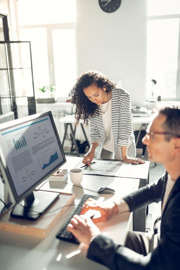 Курчавое положение секретарши около ее босса работая на компьютере стоковая фотография