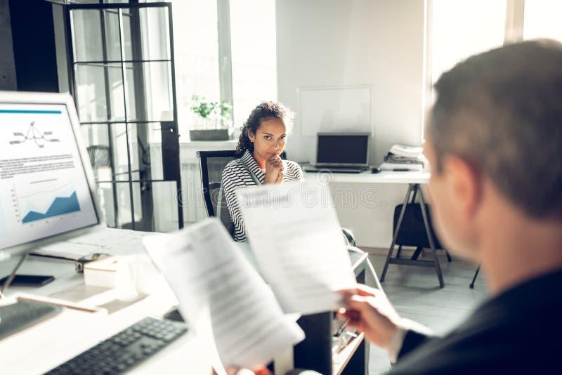 Курчавое темн-с волосами чувство секретарши потревожилось имеющ собеседование для приема на работу стоковое фото rf