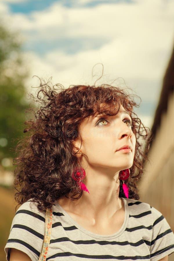 Курчавые с волосами женщины смотря вверх Лето снятое довольно женского ou стоковая фотография rf