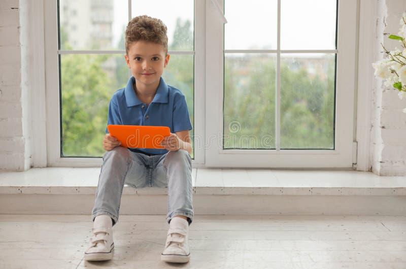 Курчавый мальчик нося стильные джинсы и белые тапки стоковое фото rf