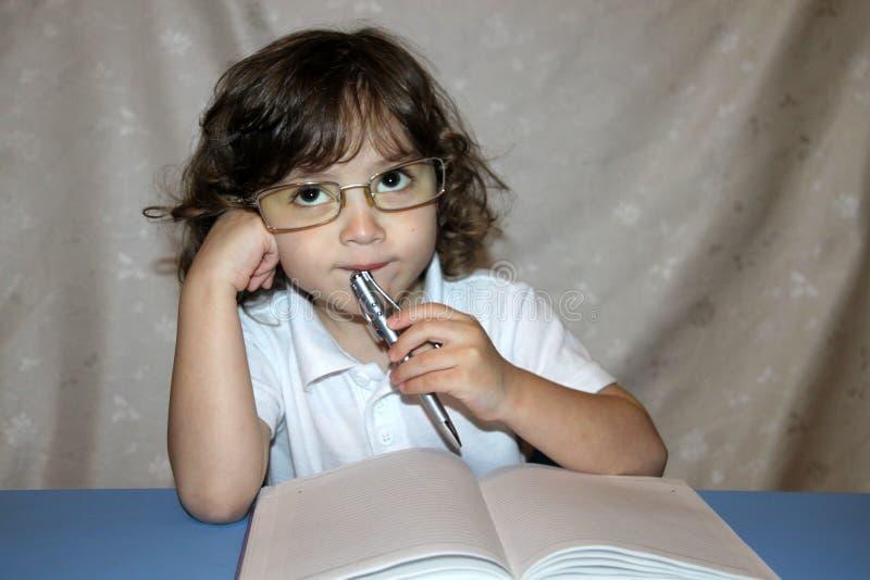 курчавый ребенок в стеклах с тетрадью и ручкой решает задачу стоковые изображения rf