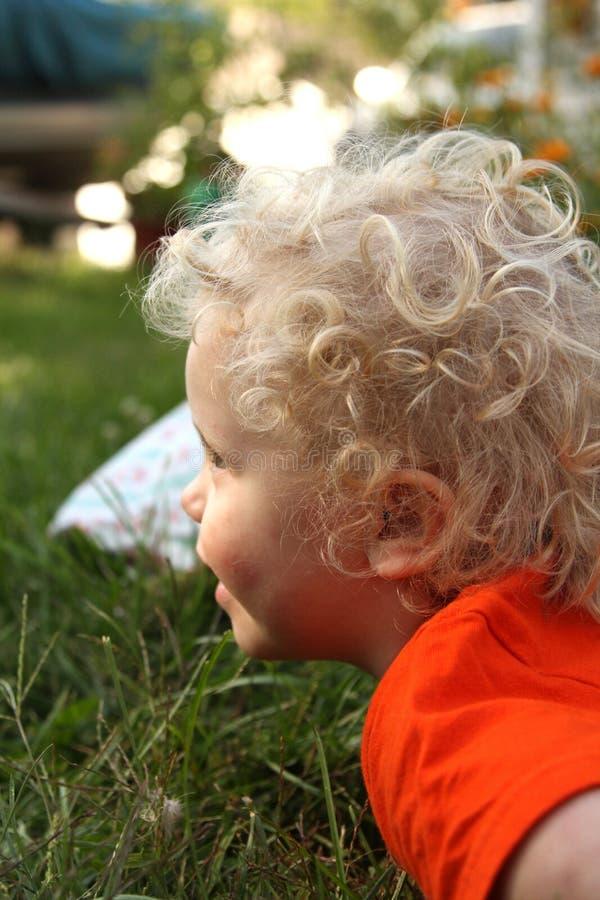 Курчавый с волосами, белокурый, усмехаясь малыш outdoors на траве в саде стоковые фотографии rf