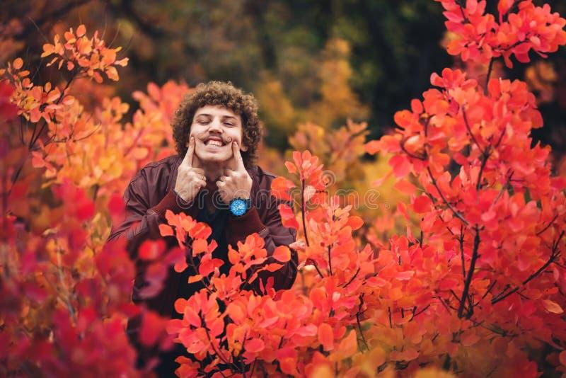 Курчавый mustachioed смешной парень протягивает его пальцы через его сторону с широкой улыбкой стоковое фото rf