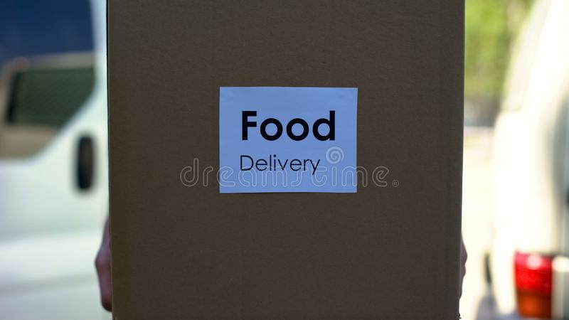 Курьер в равномерной держа картонной коробке, ходя по магазинам онлайновая служба поставки еды стоковое фото