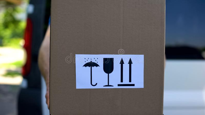 Курьер в форме держит коробку со для того чтобы держать для того чтобы высушить хрупкий этот путь вверх по знакам, обслуживание стоковое фото rf