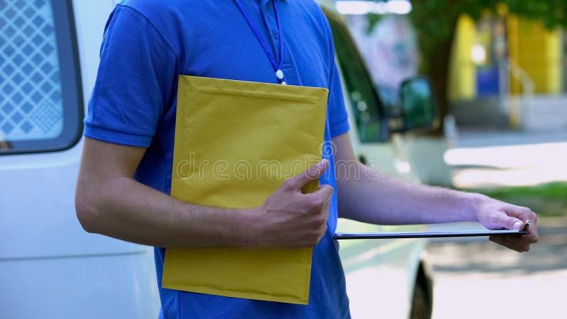 Курьер держа желтую форму доставки пакета и доказательства, грузить документов стоковая фотография