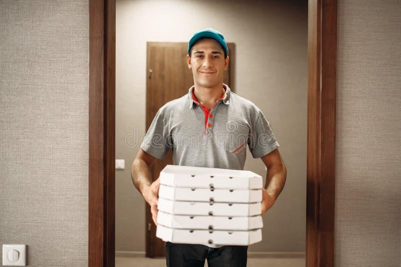 Работник доставляющий покупки на дом со свежей пиццей в коробках коробки стоковое фото