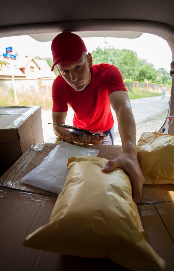 Курьер принимая пакет от багажника автомобиля стоковые фотографии rf