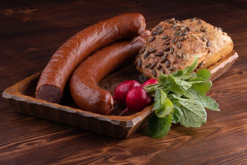 курят сосиска с хлебом и редиской, деревенской едой на деревянном столе стоковая фотография