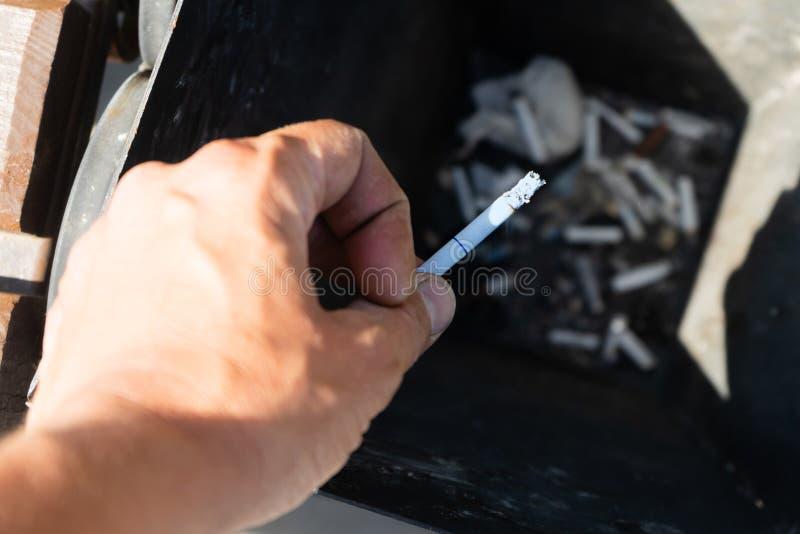 Курящ сигарету, ручная обработка сигарета в ashtray конец вверх стоковое фото