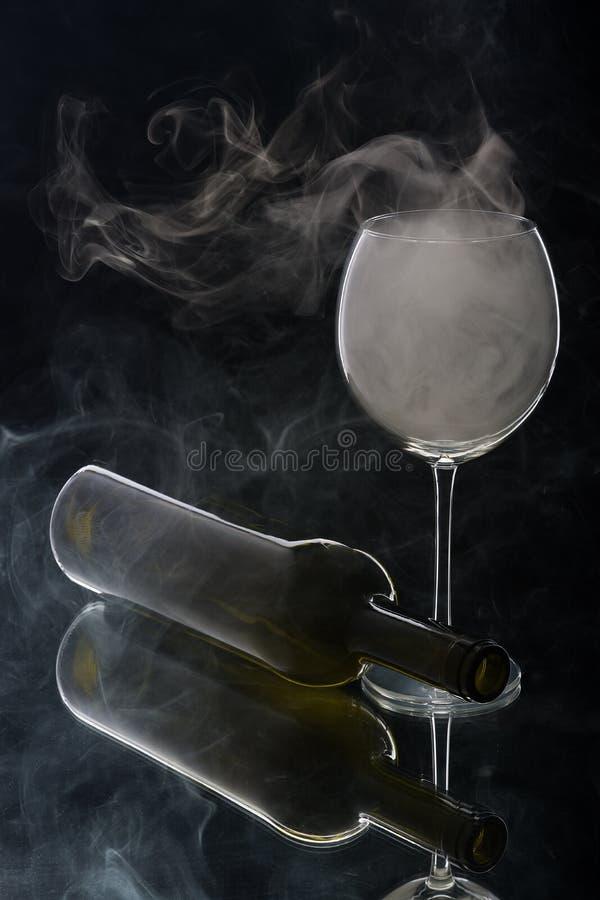 Куря бокал и лежа бутылка стоковая фотография
