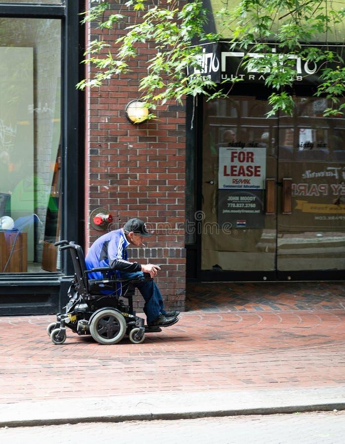 Куря человек в кресло-коляске стоковое фото rf