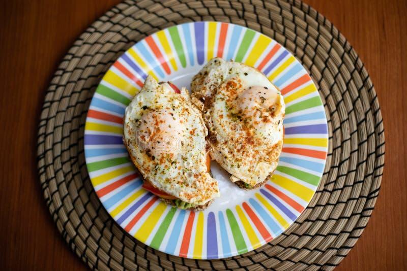 2 куска хлеба хлопьев с авокадоом, томатом и яичницей на верхней части, представленной на красочной плите на завтраке деревянного стоковые изображения rf