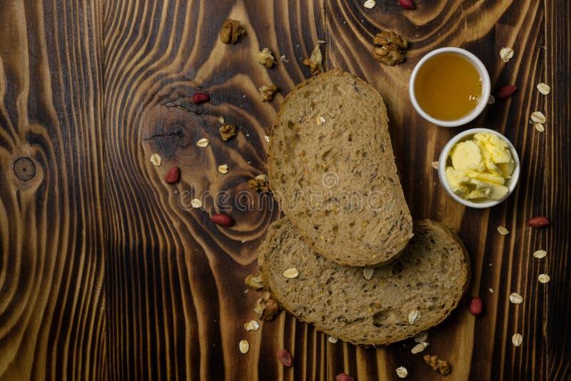 2 куска хлеба и чашки меда и масла лежа на деревянной предпосылке стоковое изображение
