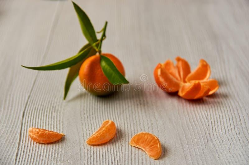 3 куска tangerine оранжевых на серой деревянной доске с космосом бесплатной копии Слезли апельсин мандарина и свежий сырцовый tan стоковое фото rf